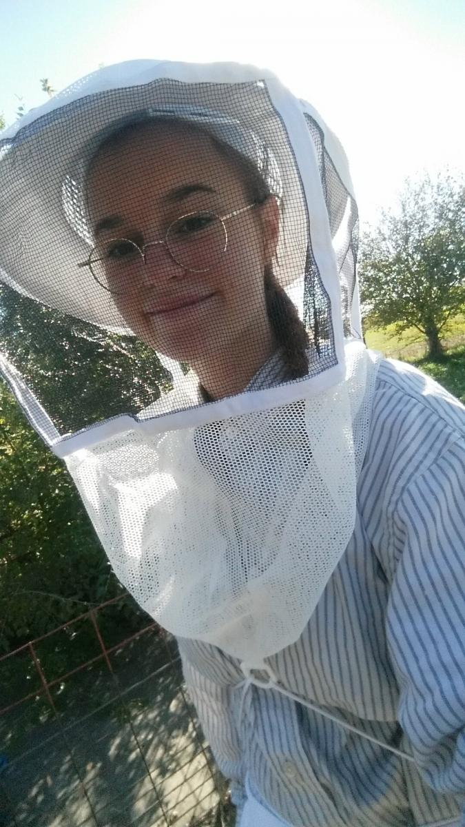 Helen smiling in her beekeeper suit and veil