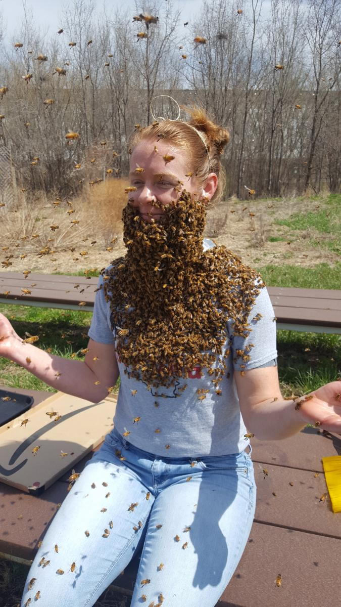 Katie sitting on bench with bees swarmed on her face, looking like a beard