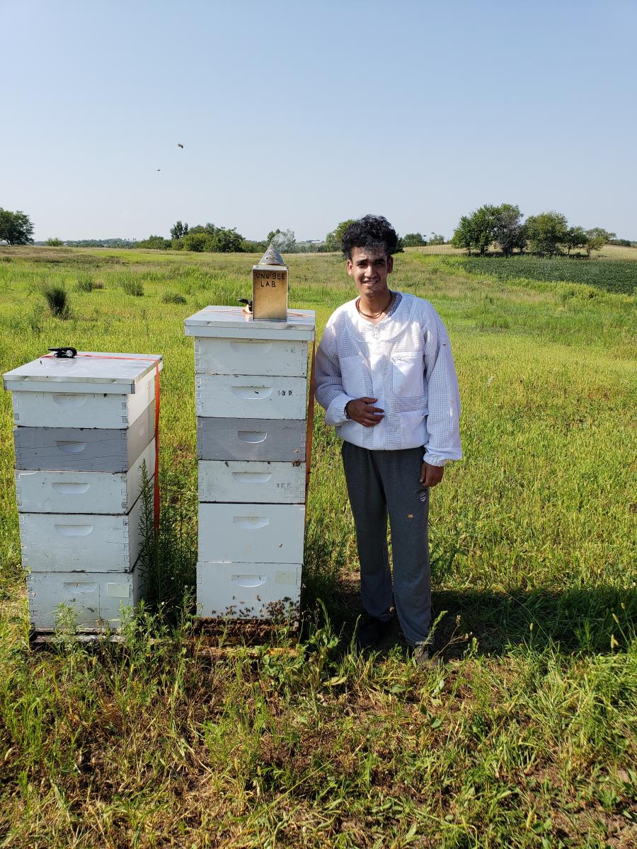 Sushant standing by stack of hives and a smoker